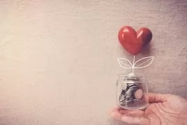 Main tenant un bocal rempli de pièces avec un coeur